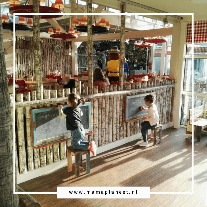 jonge kinderen tekenen op schoolbord en kijken naar Bollo in Landal Het Vennenbos