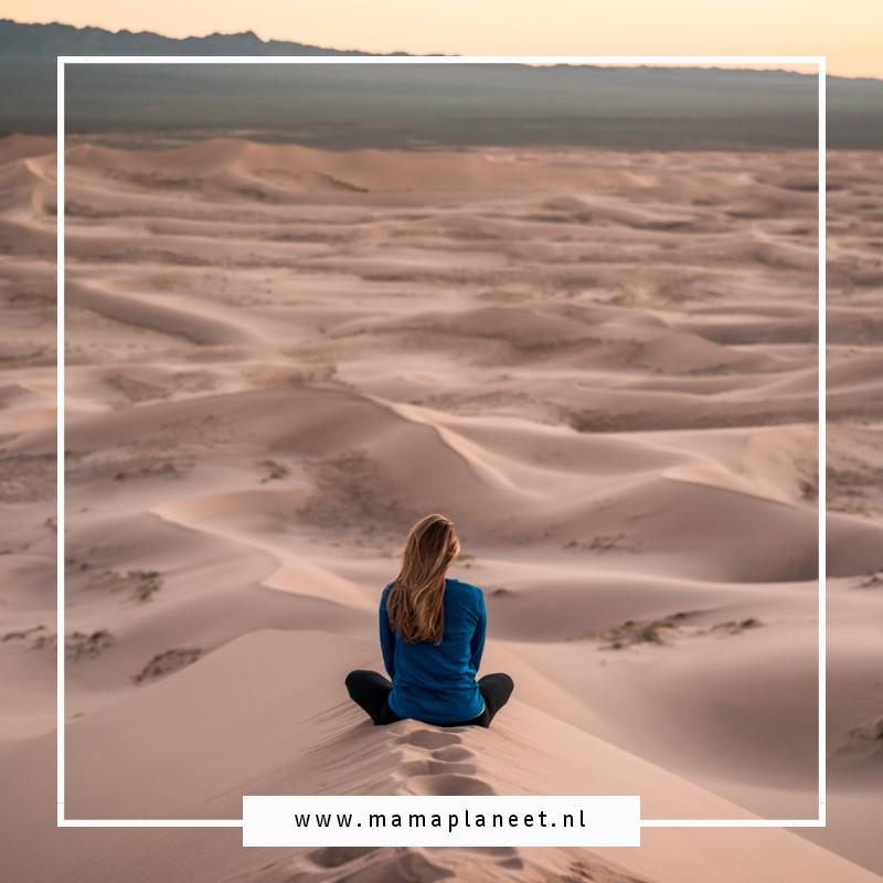 eenzame vrouw en moeder zit alleen in het zand
