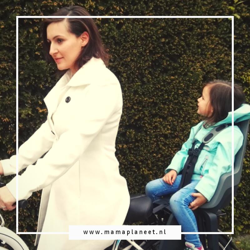 moeder fietst met haar dochter in een bobike fietsstoeltje achterop