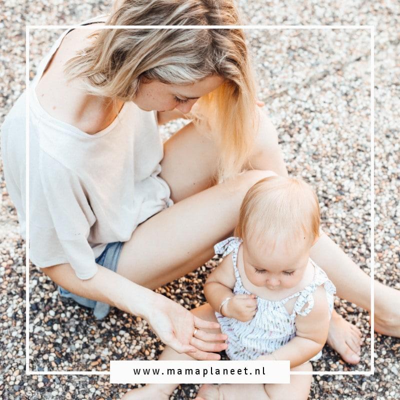 vrouw zit met baby op stenen grond