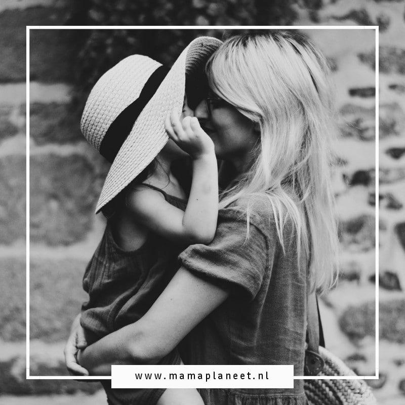 blonde vrouw houdt kind met hoedje vast in armen