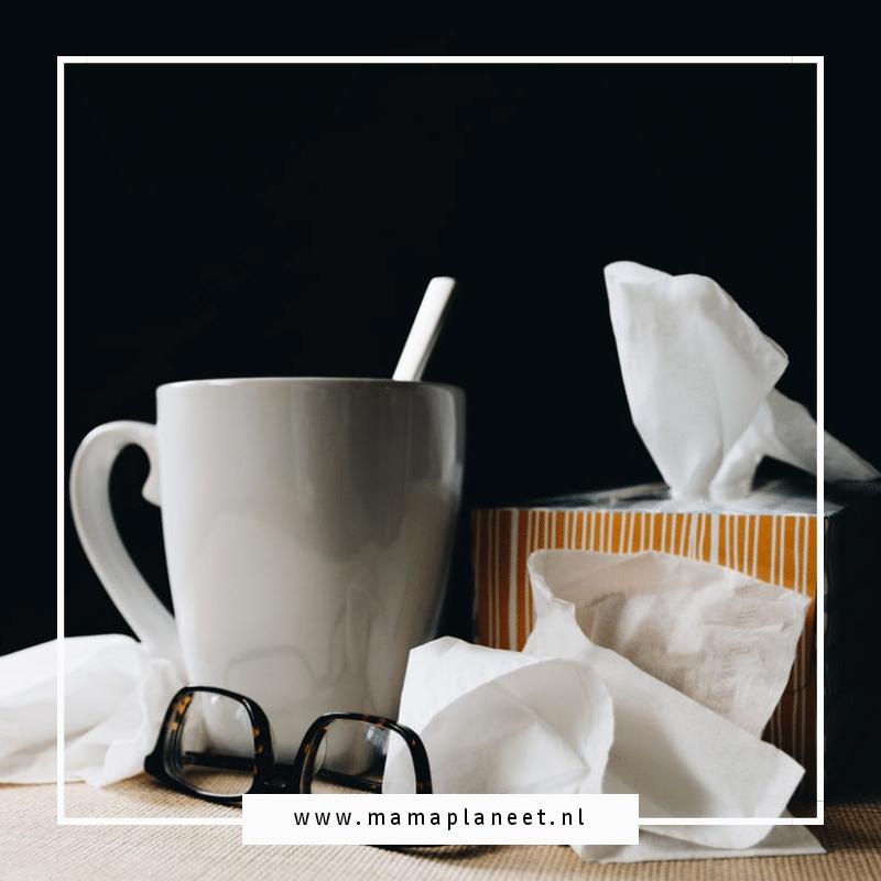 beker met thee met honing en zakdoekjes tijdens de verkoudheid