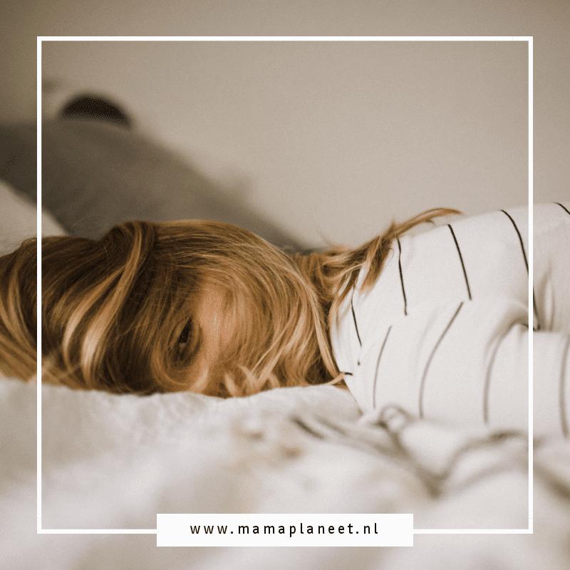 chronisch vermoeide moeder valt op bed na een lange dag met haar peuterpuber