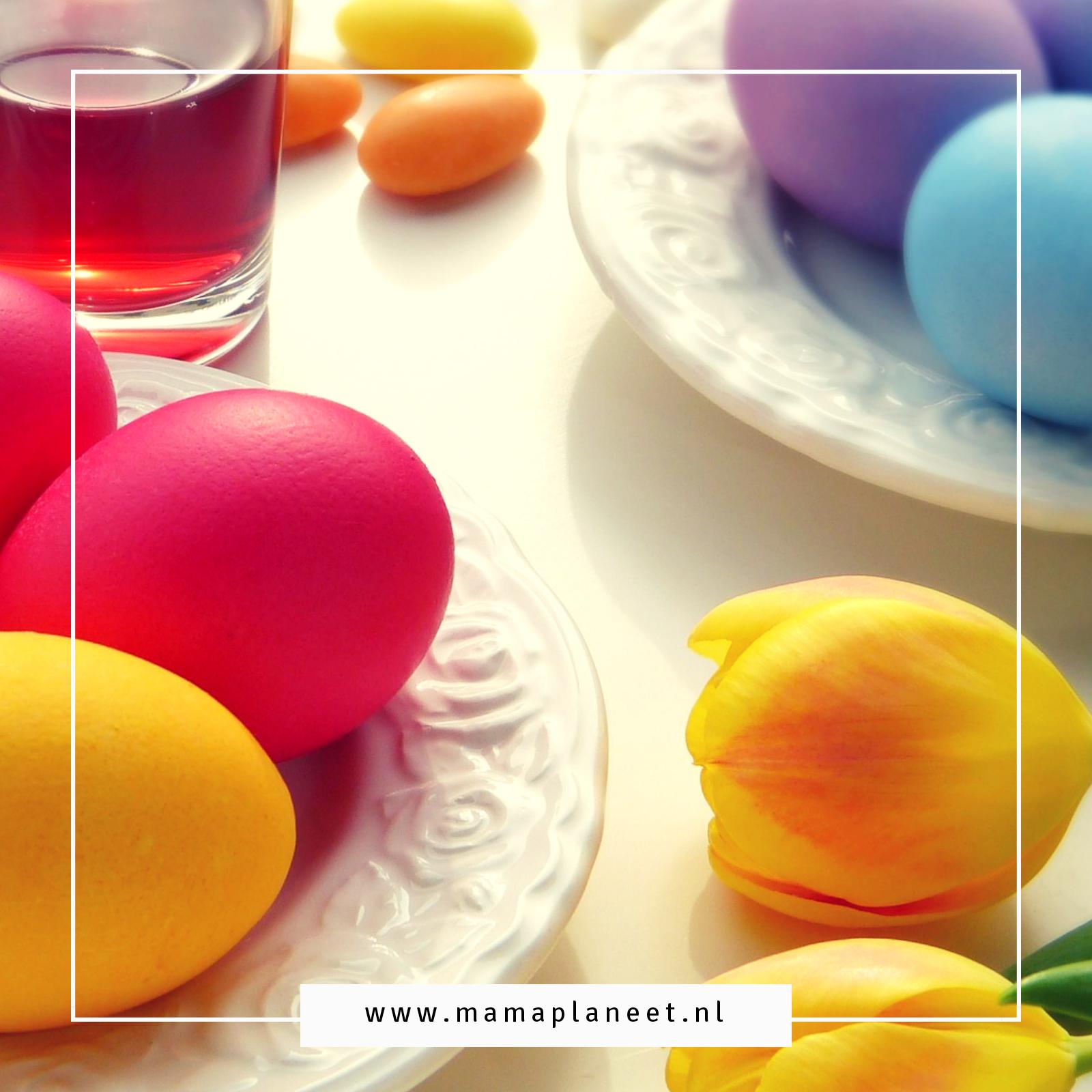 gekleurde eieren en gele tulpen op tafel voor Pasen
