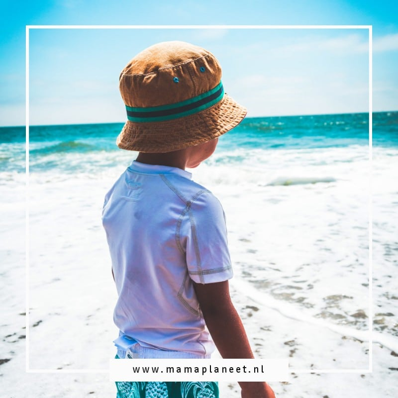 jongetje met uv-werende kleding en zomerhoed staat met zn voeten in zand naar de zee te kijken