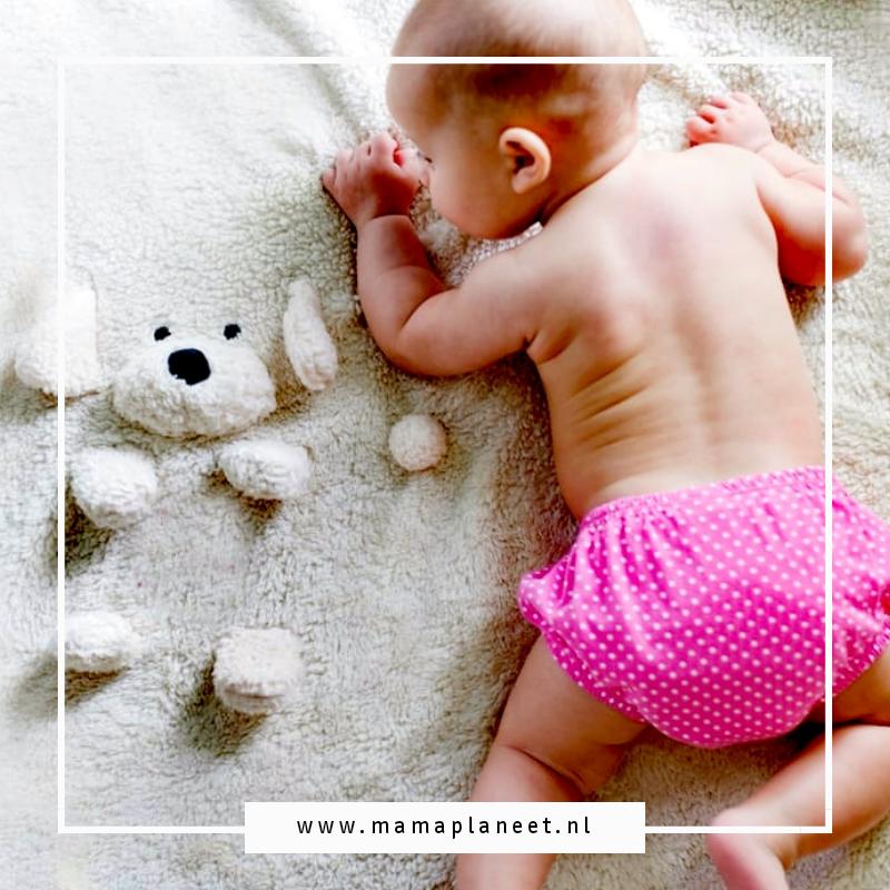 babyuitzet checklist bestaat vaak uit dingen die je makkelijk kunt missen. Baby met roze luierbroekje om ligt op haar buikje op een witte deken met hondje