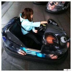 klein meisje in de zwarte botsauto