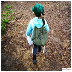 Meisje met groene met en groene rugzak loopt op een bospad