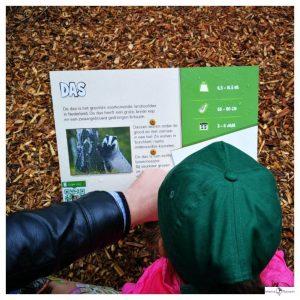 kind lees een kaart met daarop informatie over een dier samen met haar papa