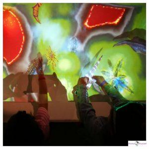 zandbak met projectie waarin kinderen spelen