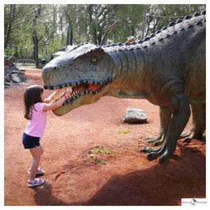 kind aait dinosaurus en telt de tanden in zijn bek