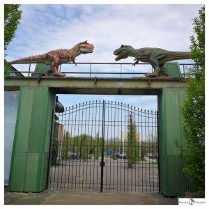 hoge groene hek met 2 dinosaurussen bovenaan