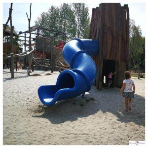 kind loopt naar de grote blauwe glijbaan