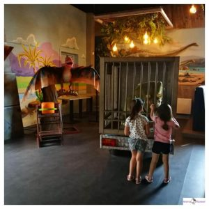 2 kinderen staan voor een kooi met baby dinosaurus in en een vliegende dino ernaast