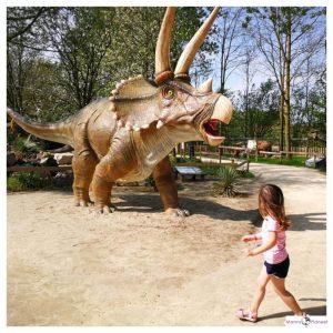 klein meisje loopt langs een dinosaurus