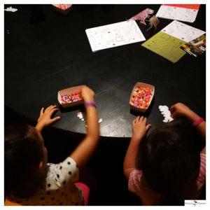 2 kinderen zitten aan tafel kralen te strijken