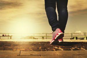 vrouw in spijkerbroek en sportschoenen