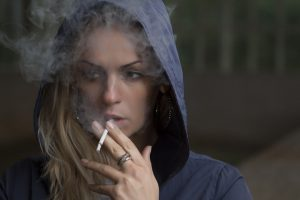 rokende vrouw met capuchon op