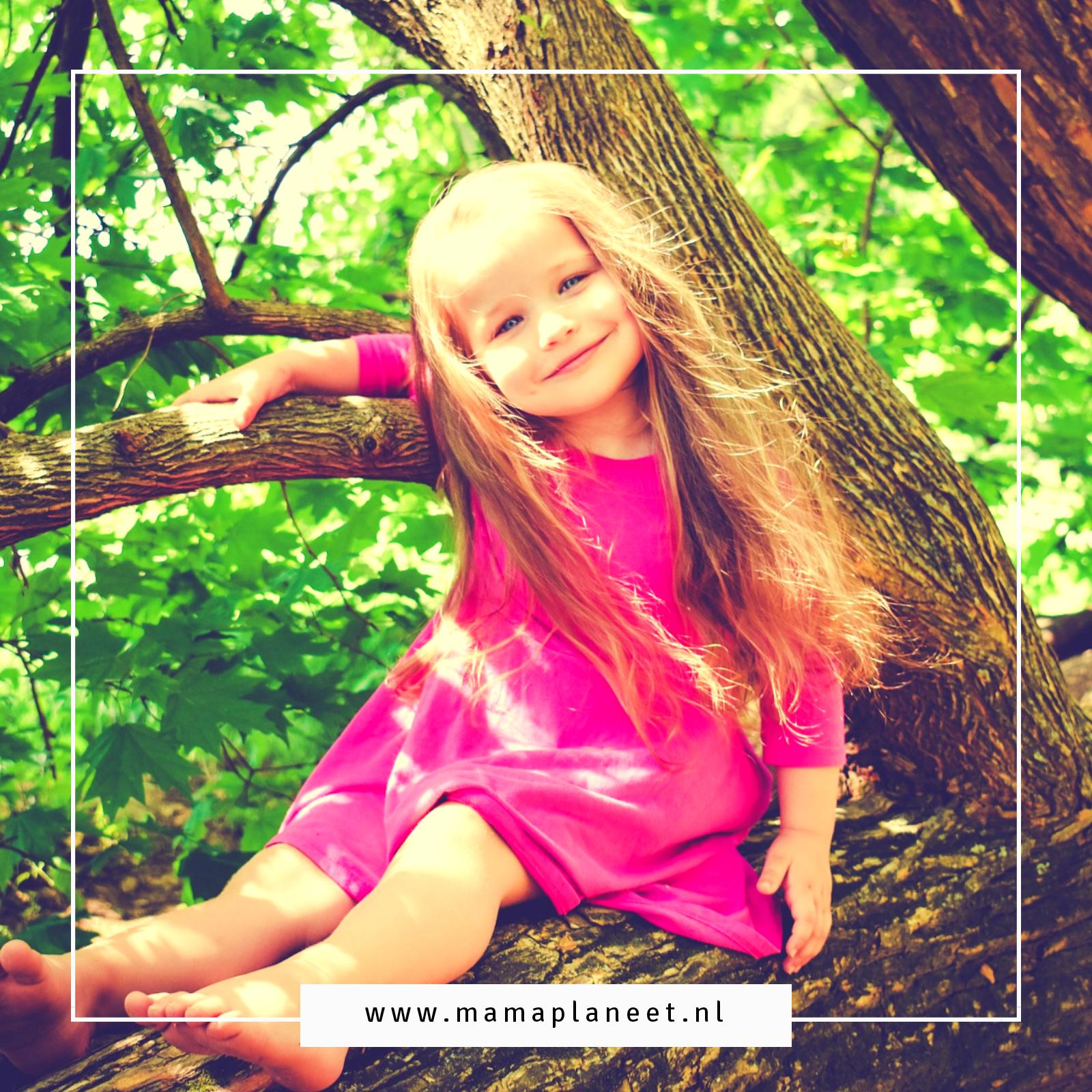 blonde peuter met lang haar en roze jurkje zit in de boom