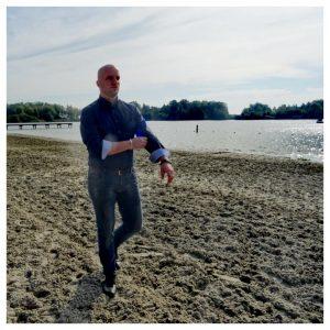 man in een strijkvrije OLYMP overhemd loopt op het strand