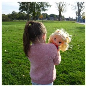 meisje met een roze vest houdt haar baby alive babypop vast