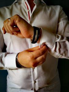 Man met een witte overhemd knoopt de mouwen dicht