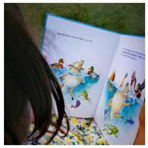 Kleuter houdt een prentenboek vast met daarin een illustratie van een zwemmende schaap