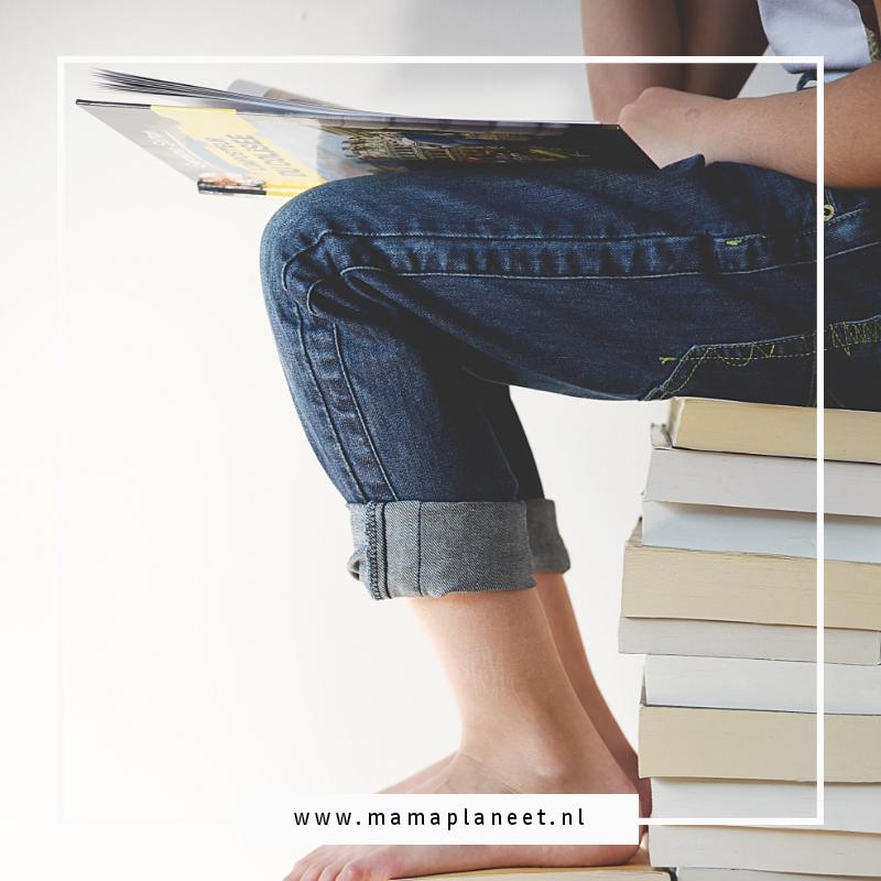 basisschoolkind met opgerolde spijkerbroek zit op een stapel boeken te lezen op AVI-niveau