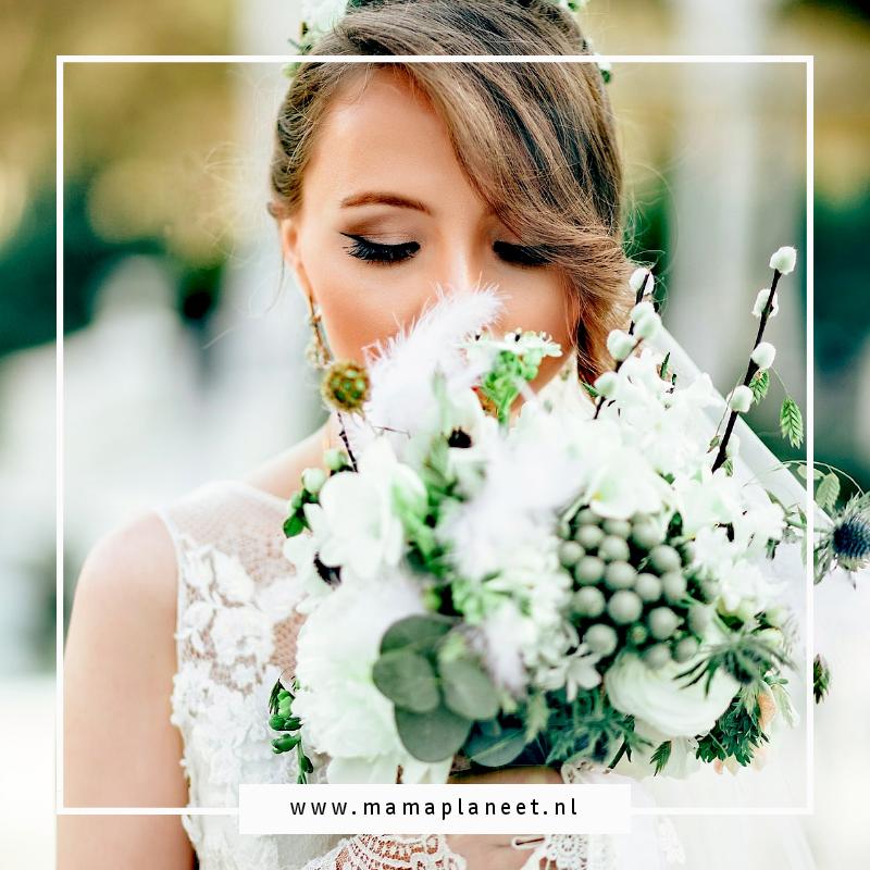 blonde vrouw in trouwjurk houdt trouwboeket in handen