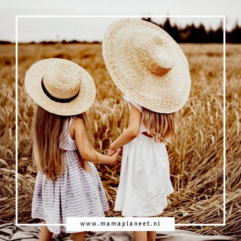 2 meisjes, zusjes in jurkjes en hoeden op staan in een maisveld in de vertel te kijken. voordeel en nadeel van kinderen zelf kleding laten kiezen om eigen kledingstijl te ontwikkelen