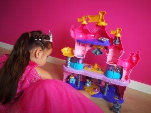 peuter, kleuter meisje in roze prinsessenjurk speelt met vrolijke vriendjes magisch lichtkasteel speelset