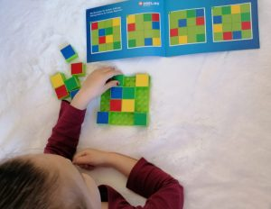 kleuter meisje speelt denkspel sudoku met kleuren