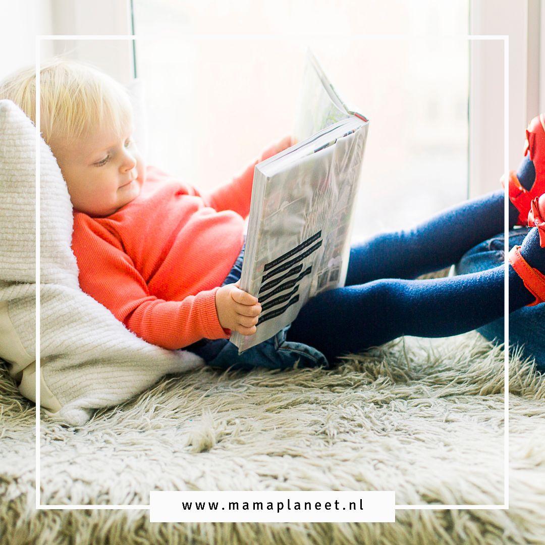 peuter kijkt in een boekje in de leeshoek voor kinderen MamaPlaneet.nl